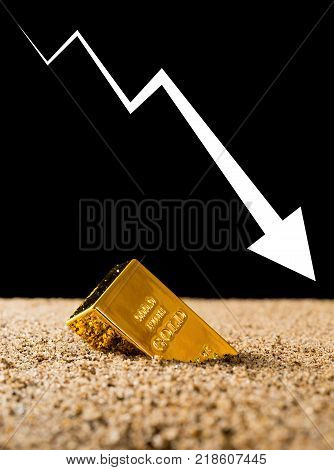 gold bar sinking into sand with a big downwards arrow on black background concept of gold price and investment
