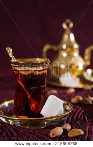 Closeup of Tunisian tea in traditional glass with sugar cube and pine nuts