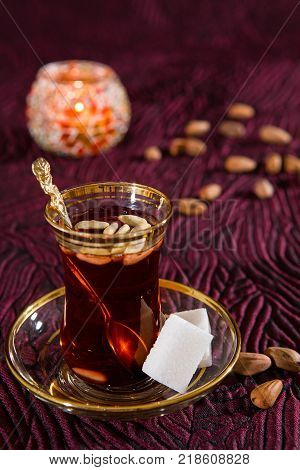Tunisian tea in traditional glass with sugar cube and pine nuts