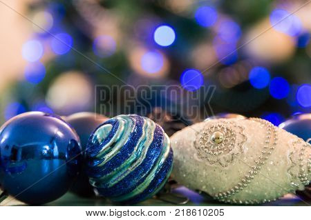Decorated Christmas tree with blue lights. Christmas balls in the foreground. Blurred image of a Christmas tree in the background.