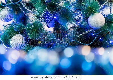 Decorated Christmas tree with blue lights. White Christmas ball and garland. Unfocused image in the foreground.