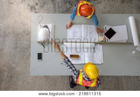 Top view of group of professional engineering team wearing safety helmet is meeting and pointing finger up , planning construction work, looking paper plans at construction site, overhead view,Concept for team work