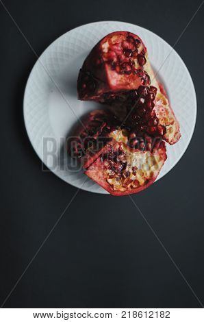 Ripe freshness red pomegranate with seed, grains on white plate on dark background. Dissected pomegranate on pieces.