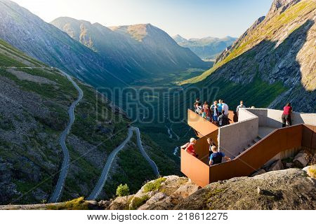 Rauma Municipality Norway - 25 July 2013: people on observation deck over Trollstigen mountain road. Serpentine road with cars and mountains in background. Popular tourist destination in Scandinavia Europe.