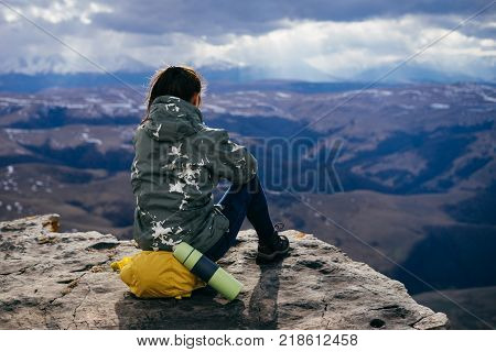 a young girl in a warm jacket sits on the edge of the mountain, enjoying nature and clean air, tea in a thermos