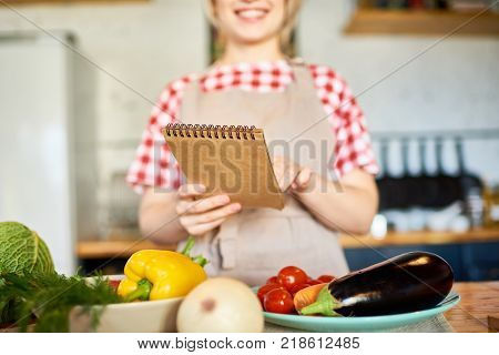Mid section portrait of smiling young woman reading recipe or grocery list while cooking in modern kitchen, focus on foreground