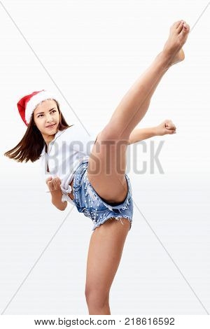 Beautiful girl in a Santa Claus hat is beating kick