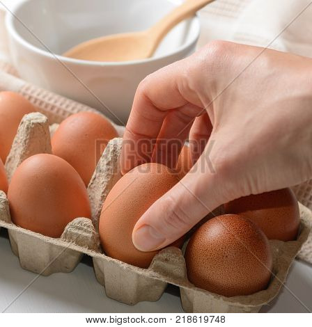 Woman hand taking an egg from a paper mould box