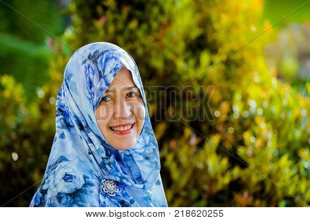 Indonesian muslim model wearing hijab with green nature background