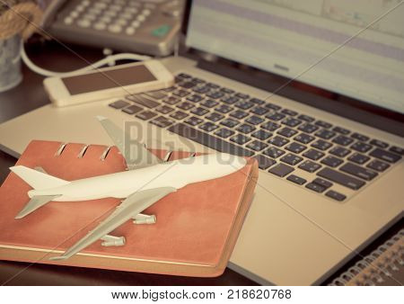 Plane on working desk for business travel and travel agency concept