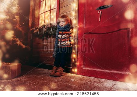 Cute little boy in winter clothes stands on the porch of the magic house of Santa Claus. Miracle time. Merry Christmas and Happy New Year.