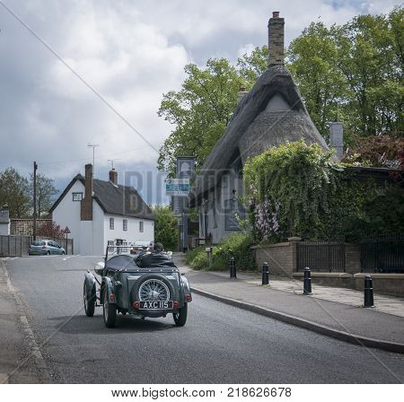 FOWLMERE, CAMBRIDGESHIRE, UK, MAY 2017 - View of a vintage Wolesley Hornet car driving through the pretty village of Fowlmere Cambridgeshire England UK