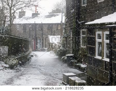 the village of heptonstall a yorkshire village in winter with falling snow