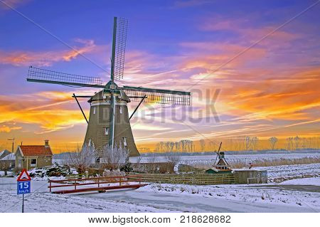 Historical windmill in the countryside from the Netherlands in winter at sunset