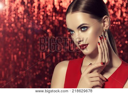 Beautiful model girl with red and black  french manicure on nails . Fashion luxury makeup . Dark red lips and shiny eye shadow pigment . Beauty  and cosmetics . Red shiny background