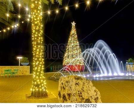 Christmas tree, water fountain, illuminated palm tree with strip lights on a pedestrian street of Camana Bay Grand Cayman, Cayman Islands, Dec 2017