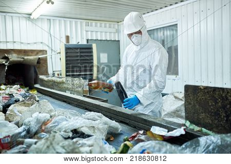 Portrait of worker  wearing biohazard suit and hardhat working at waste processing plant sorting recyclable materials on conveyor belt