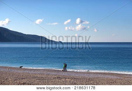 OLUDENIZ, TURKEY - November 5, 2017: Tourists walking with dogs on the Belcekiz beach
