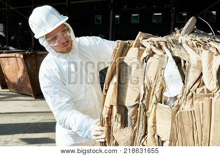 Portrait of factory worker wearing biohazard suit sorting reusable cardboard on waste processing, copy space