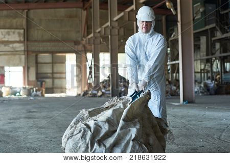 Portrait of man in hazmat suit carrying bag of recyclable materials in warehouse of waste processing plant, copy space
