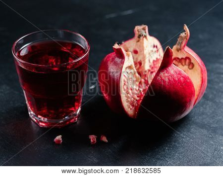 sliced pomegranate and juice on dark background. Fiber, vitamin C, vitamin K and potassium source. Healthy food and organic fruit concept