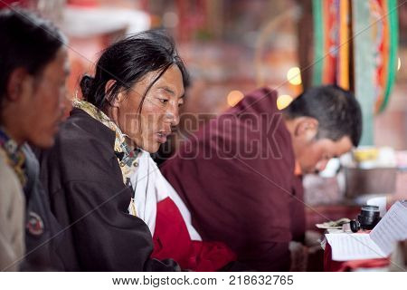 NGARI, TIBET, CHINA - APRIL 28, 2013: Buddhist monks praying during Puja ceremony in Chiu Gompa, Western Tibet