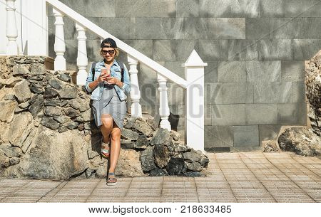 Young woman using smartphone at travel location - Fashion blogger girl sharing content with mobile smart phone on the go - Modern tourist wander lifestyle concept on social media network communication
