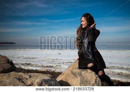Young beautiful woman in elegant clothes with scarf sits on the coastline in winter season and looking away. 1 person