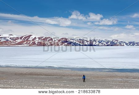 An unidentified tourist walking on shore of Rakshas Tal lake in Western Tibet China. This lake also known as Demons Lake Ravana Tal or Ravan Harda in Hindu Religion.