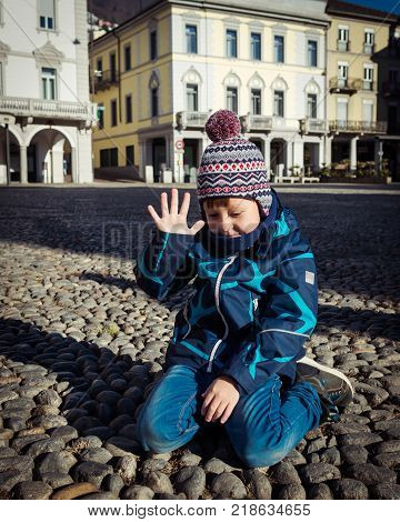Beautiful little boy is sitting on the ground and shows that he is five years old in this sunny winter day. 1 person
