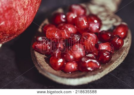 Pomegranate kernels with rustic indian spoon on dark background