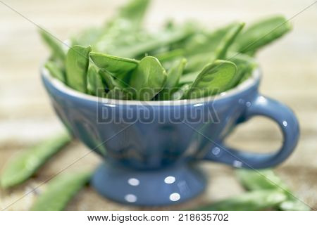 Sugar pods with rustic background and blue Cup
