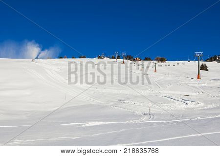 Chairlift without people. The cable car on the blue sky in the Dolomites. Cableway in the mountains without people. Artificial snowing ski slope by Snow cannon maker. Alpe di Siusi, Italy in winter.