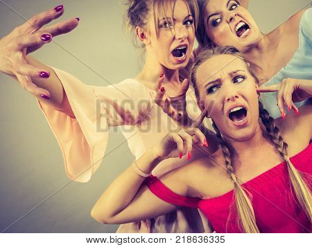 Woman being bullied by her two female friends. Women having argument. Angry fury girls screaming at her friend or younger sister. Friendship difficulties rivaly and envy problems.