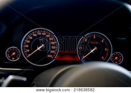 transport concept - close up. car panel instrument red speedometer and tachometer
