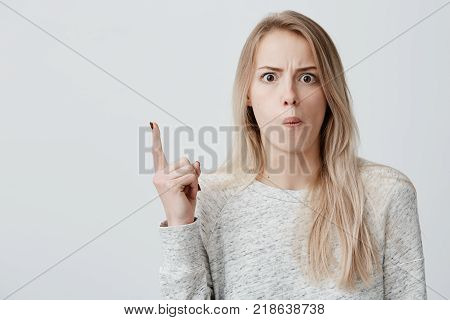 Amazed female model with straight dyed blonde hair, wearing casual clothes, looking with bugged eyes at camera, pointing with forefinger at copy space for your text or advertisment above her head