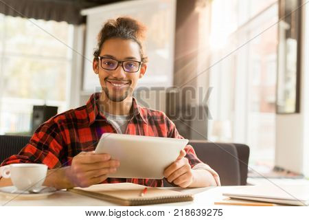 Successful young manager with tablet looking at camera while browsing in cafe