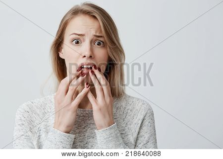Portrait of surprised amazed attractive young blonde with dyed hair female wearingsweater having astonished face expression, covering her open mouth with hands, looking at camera in shock and full disbelief