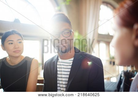 Young intercultural man and woman listening to their colleague explanations at business meeting