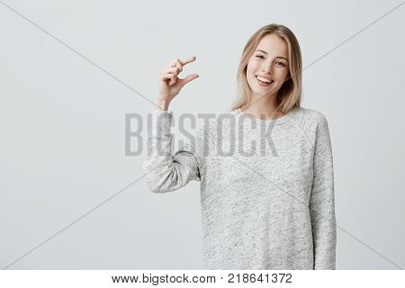 Positive beautiful fair-haired female in loose sweater shows something small in size with hands, has good mood, isolated against gray background. Good-looking young woman smiles happily at camera