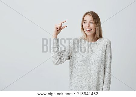 Glad beautiful blonde pretty woman in loose sweater shows something small with hands, glad to play with little kid, isolated against gray background. Good-looking young female demonstrates size of heel