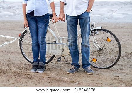 A pair of lovers spending time on the ocean. Beautiful brunette girl rides a bicycle