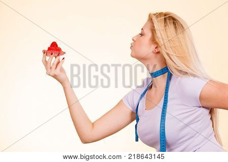 Diet and slimming temptation unhealthy food concept. Woman with measuring tape around her neck holding strawberry sweet cupcake