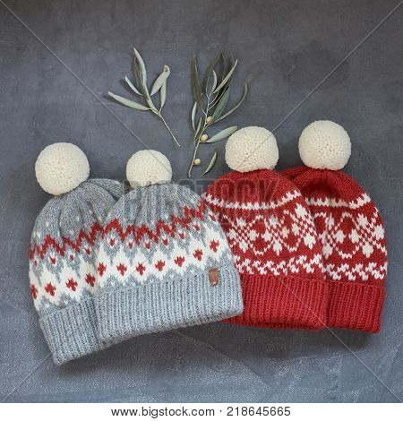 Four knitted hats two gray and red owl with a jacquard pattern on a gray background closeup.