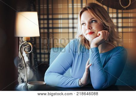 Blond woman in blue dress have rest in cafe