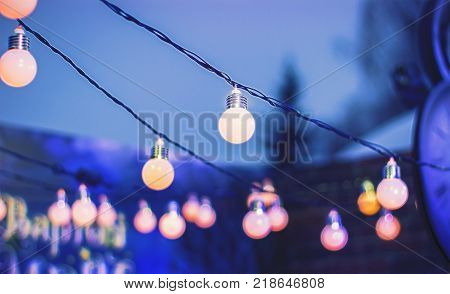 Decorative outdoor string lights hanging in the garden at night time