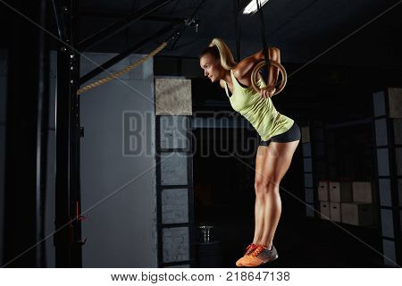 Horizontal shot of a female athlete performing ring dips exercise at the gym. Gorgeous young blonde training at fitness gym using gymnastic rings determination motivation healthy strong
