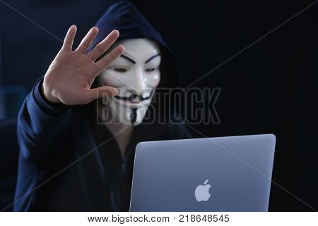 MYKOLAIV, UKRAINE - SEPTEMBER 29, 2017: Anonymous person in Guy Fawkes mask using laptop on black background