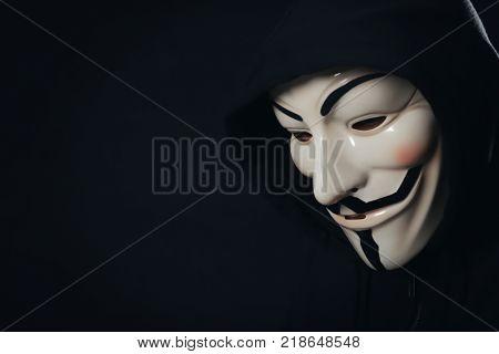 MYKOLAIV, UKRAINE - SEPTEMBER 29, 2017: Anonymous person in Guy Fawkes mask on black background