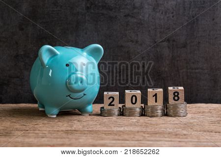 Year 2018 financial goal with piggy bank and stack of coins and on top by wooden cube block with number 2018 on table and dark black background with copy space.